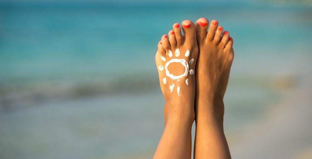 Sonnencreme auf einem Fuß