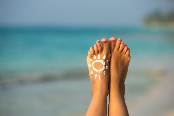 Fuß mit Sonnencreme