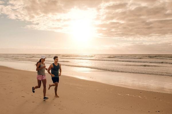 Frau und Mann joggen am Strand