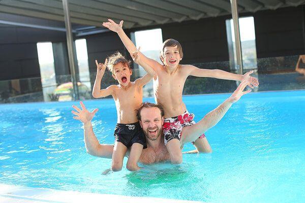 Vater mit Kindern im Schwimmbad an der Ostsee