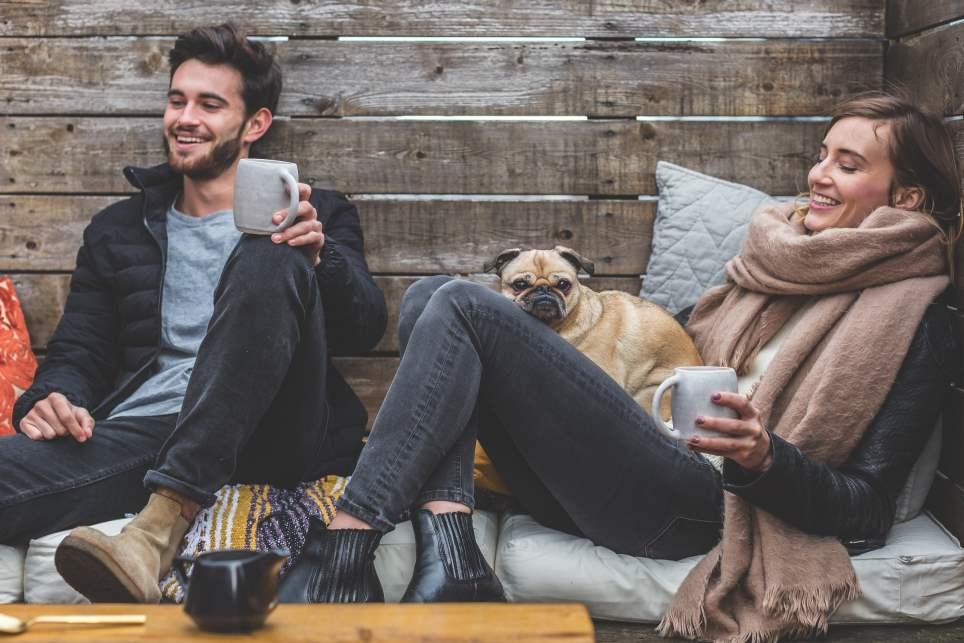 Paar mit Hund in rustikaler Holzhütte