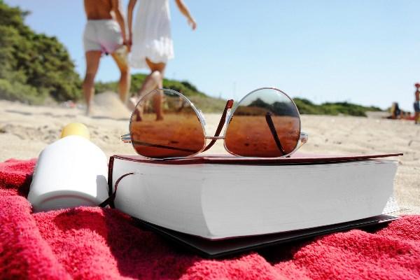 Strandtuch mit Buch und Brille
