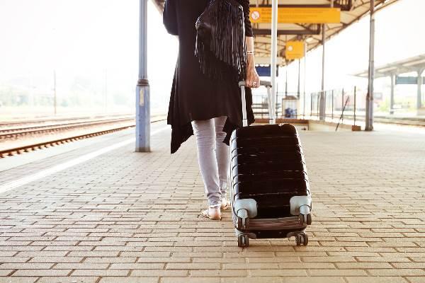 Frau rollt Koffer auf Bahngleis