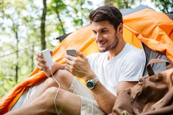 Camper mit Smartphone und Powerbank
