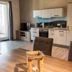Wohnzimmer mit Flat-TV und Küche