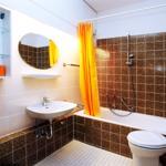 Das Bad mit den Originalfliesen und modernen, hochwertigen Armaturen