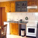 Küche mit Herd, Kühlschrank, Wasserkocher, Kaffeemaschine, Geschirr für 4 Personen