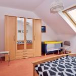 Schlafzimmer mit Doppelbett und Kinderbett. Bettwäsche optional.