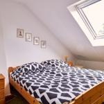 Schlafzimmer mit Doppelbett und Einzelbett. Bettwäsche optional.