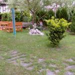 Holzsitzgruppe im Garten unter der Weide am Bachlauf mit Wasserspiel und Teich