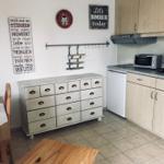 Küche mit Mikrowelle, Backofen, Herd und Kühlschrank mit Gefrierfach