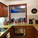 Küche mit Induktions-Kochfeld, Backofen, beleuchtetem Geschirrspüler und vielen Kleingeräten