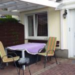 Überdachte Terrasse mit Gartenmöbel und Grill.