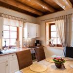 Essplatz mit offener Küche und angrenzendem Zugang zur überdachten Holzterrasse