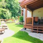 überdachte Holzterrasse mit Gartenmöbel und Grillplatz und Feuerschale