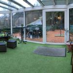 beheizbarer Wintergarten mit Lounge-Gruppe und Blick zur Süd-/Westterrasse mit festem Grill sowie Esstische