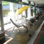 Im Schwimmbad am Beckenrand befindliche Liegestühle sowie beheizte Bänke zur Ruhe und Entspannung mit großer Glasfront. Geschützter Ausblick
