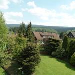 Panoramablick vom Balkon auf Teile des Hausgartens und der umliegenden Berge