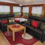 Wohnzimmer mit gemütlicher Sitzecke. Der Fernseher und Kamin ist gegenüber