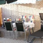 Terrasse vor dem sep. Eingang der Ferienwohnung mit Markiese und Sonnenschirm.