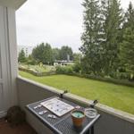App. 1: Blick vom modern möblierten Balkon auf die großen Wiesenflächen im Ferienpark