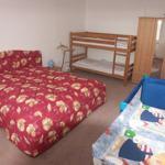 großes Schlafzimmer der Wohnung 1 mit breitem Doppelbett, Doppelstockbett und Reisebett mit Wickeltisch