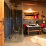 Bad mit Fußbodenheizung, Natursteinwaschtisch, Handtuchheizkörper, Regendusche und eigener finnischen Sauna