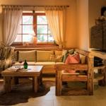 offener uriger Wohnbereich mit aufgearbeiteten Altholzmöbeln und Kamin