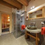 ebenerdiges Bad mit Fußbodenheizung und Natursteinwaschtisch, Regendusche sowie eigener Sauna