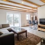 Das Wohnzimmer ist modern und stilecht mit Balkenoptik eingerichtet.