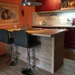 Esstresen mit Cerankochfeld und Dunstabzugshaube, dahinter der Küchenbereich.