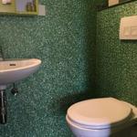 Toilette separat und direkt angrenzend ans Badezimmer mit lustig-grüner Glööckler-Tapete.