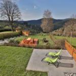 Aussicht vom Balkon auf Garten mit Liegewiese, Sitzplatz und Grillhütte