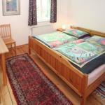 Schlafzimmer mit Doppelbett und Schrank, Tisch und 2 Stühlen. Fenster nach Westen