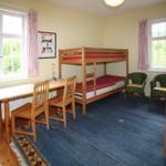 Kinderzimmer mit 2 Etagenbetten und großem Schrank. Das Zimmer hat Fenster nach Süden und Osten Richtung Garten.
