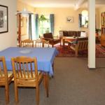 Wohnzimmer der Fewo Fuchsbau. Hier gibt es eine Sofaecke, eine Umbauliege und einen großen Esstisch
