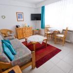 Ein gemütliches Wohnzimmer mit Couch, 81cm-Flach-TV-Gerät, Esstisch zum Ausklappen und Küchenzeile.