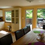 Blick über den Esstisch zur offenen Küche und Terrasse